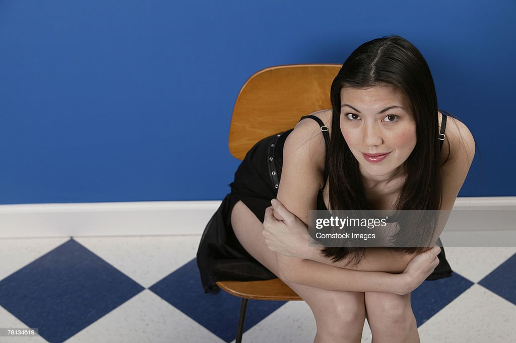 Woman in cocktail dress sitting in chair : Stockfoto