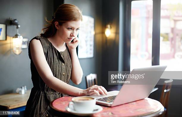Woman in coffee shop on mobile and using laptop.