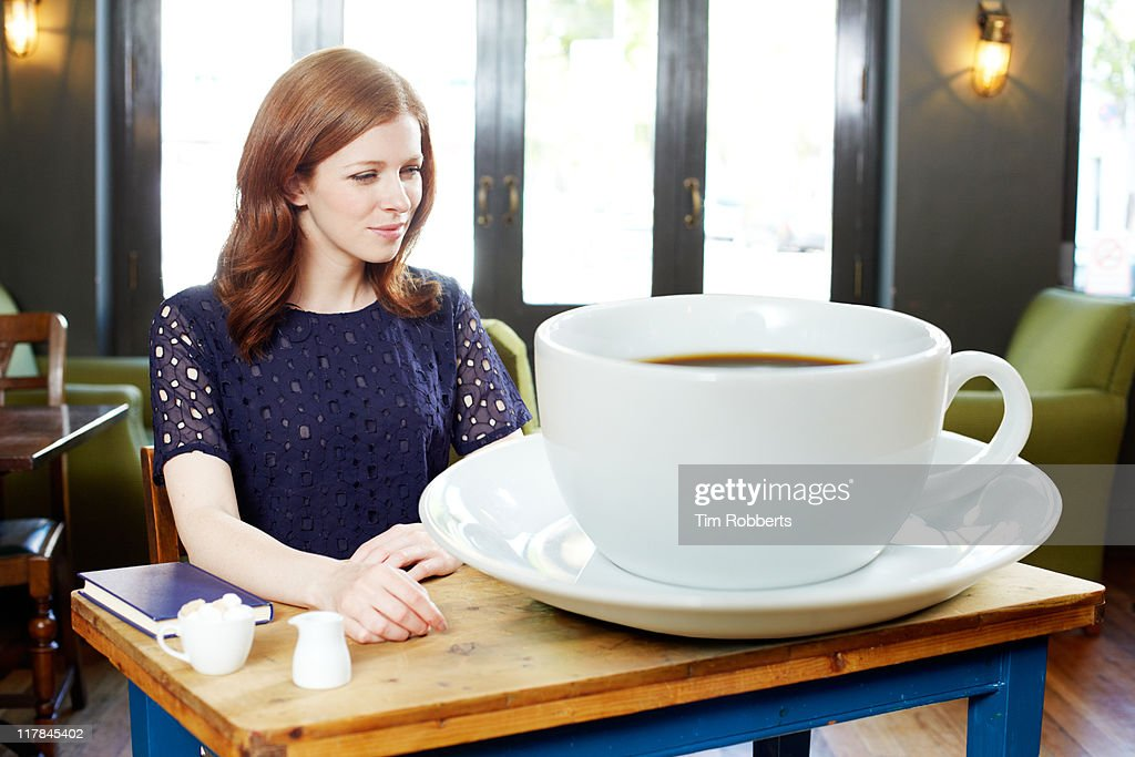 Woman in coffee shop with huge coffee. : Stock Photo