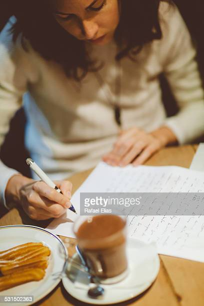 Woman in coffee shop writing on paper