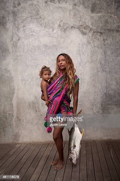 Woman in colorful wrap holds baby and big fish