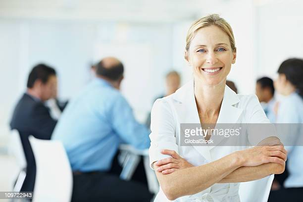 Woman in conference room with business colleagues at the back