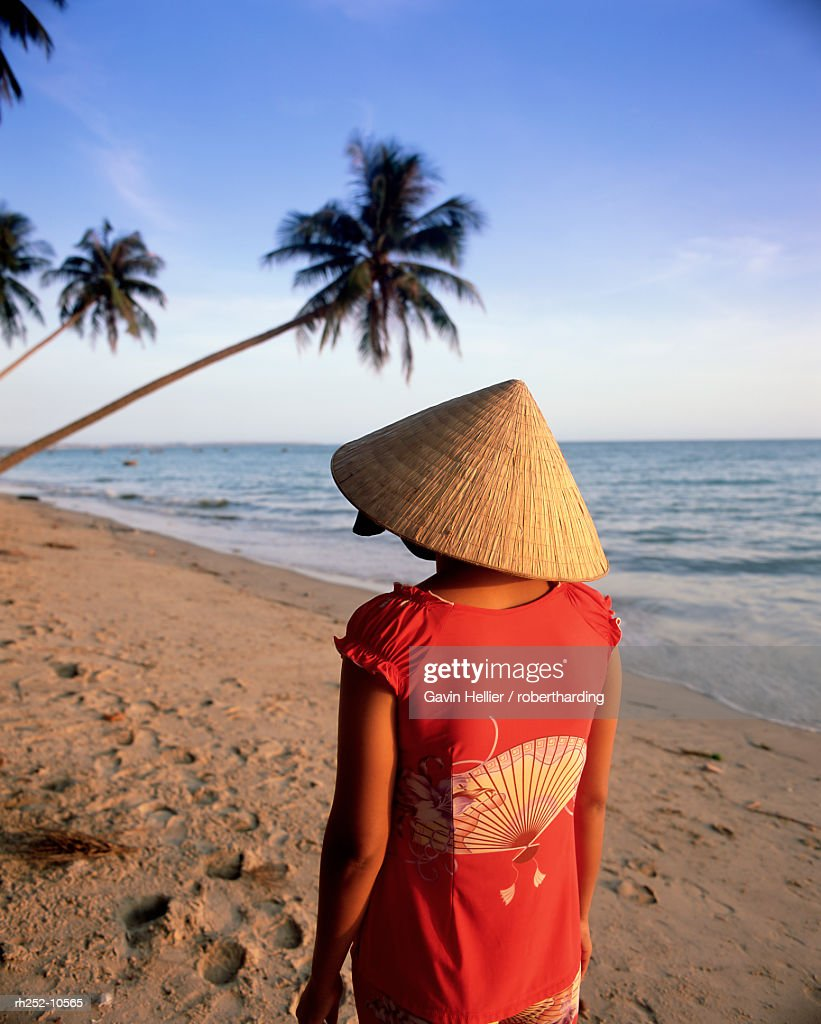 Woman in conical hat walking along the beach, Mui Ne beach, south-central coast, Vietnam, Indochina, Southeast Asia, Asia : Foto de stock