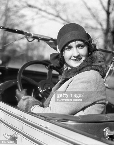 woman in convertible car wearing cloche hat coat with fur trim holding steering wheel but turned to look behind her smling. - 1920 car stock photos and pictures