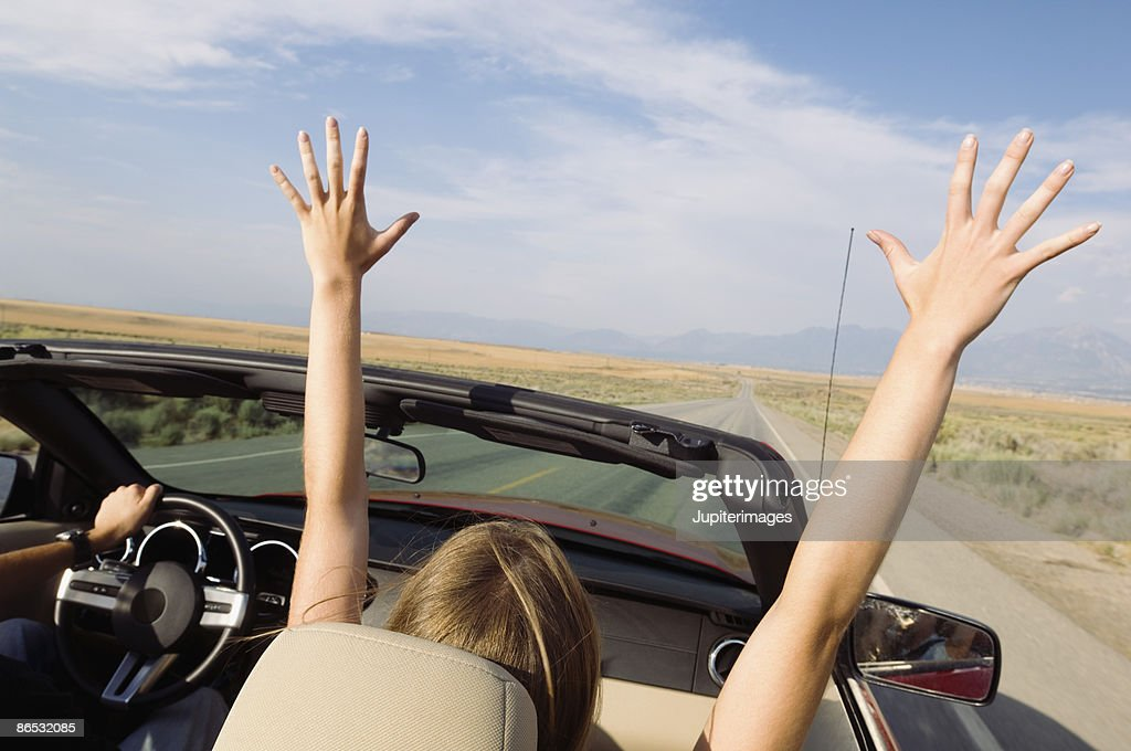 Woman in convertible with arms raised : Stock Photo