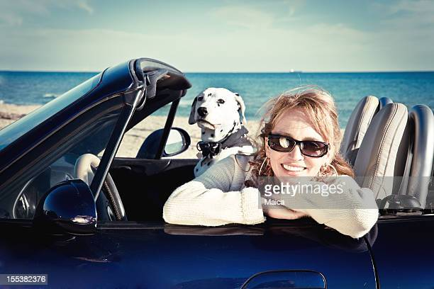 Woman in convertible with pet