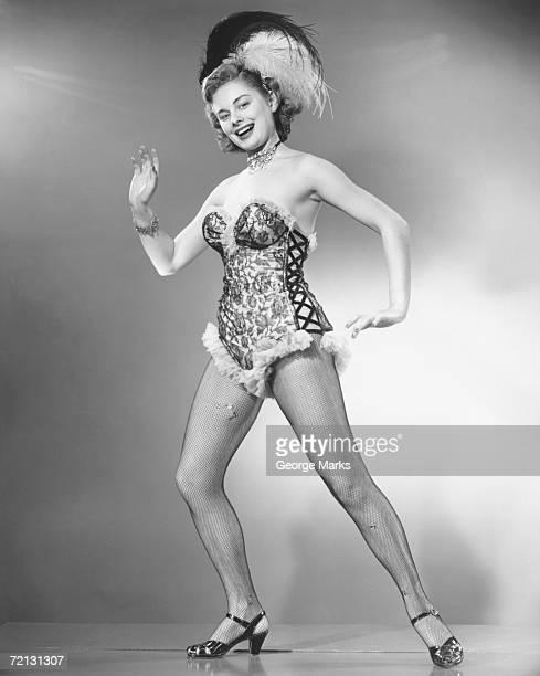 Woman in corsets and fancy hat dancing in studio (B&W), portrait