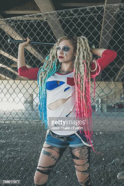 Woman In Cosplay Costume Standing Against Chainlink Fence