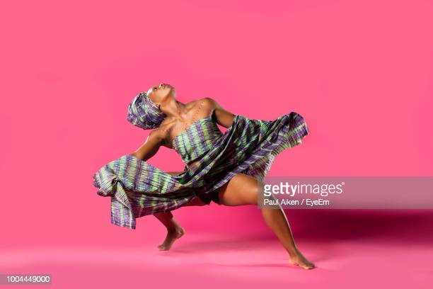 woman in costume dancing against pink background - aikāne stock pictures, royalty-free photos & images