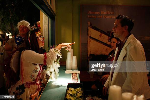 A woman in costume participating in the Fantasy Fest Masquerade March orders a drink from a bar tender October 27 2007 in Key West Florida The ten...
