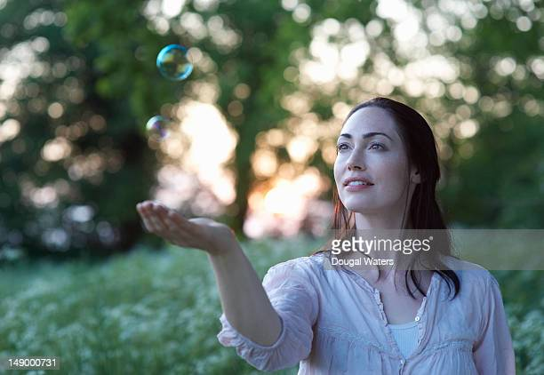 Woman in countryside watching bubble.