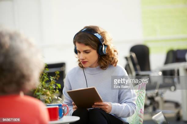 Woman in creative office listening to headphones.
