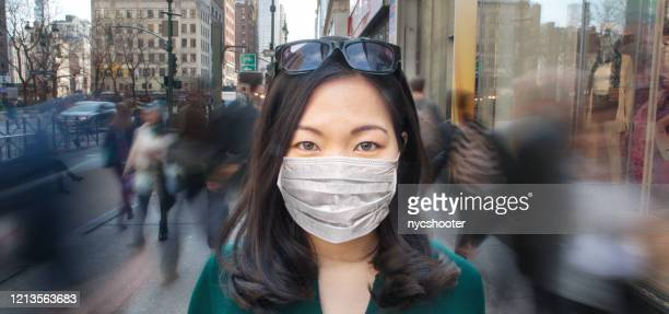 woman in crowd wearing surgical mask - moving past stock pictures, royalty-free photos & images