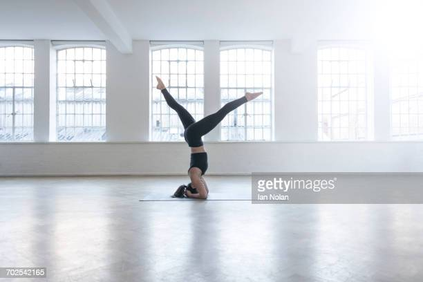 Woman in dance studio doing headstand
