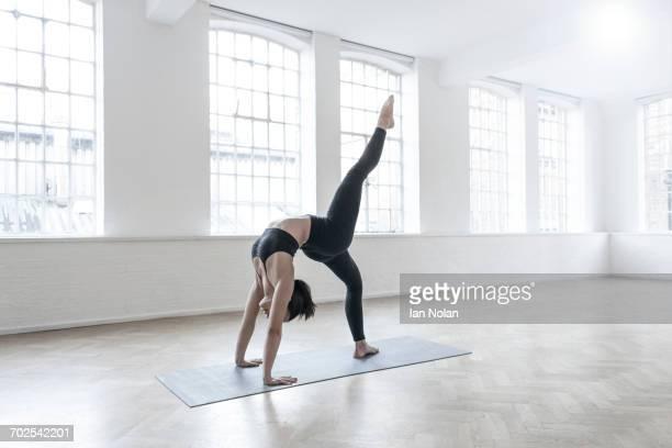 woman in dance studio leg raised in crab position - beugen oder biegen stock-fotos und bilder