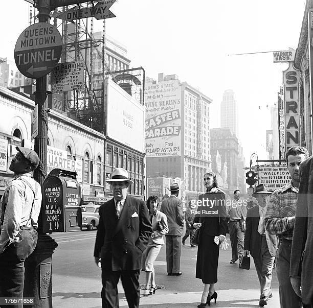 A woman in dark coat and heels stands and looks around on a busy city street New York New York 1948