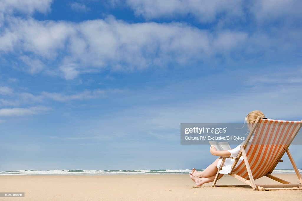 Woman in deck chair on beach : Stock Photo