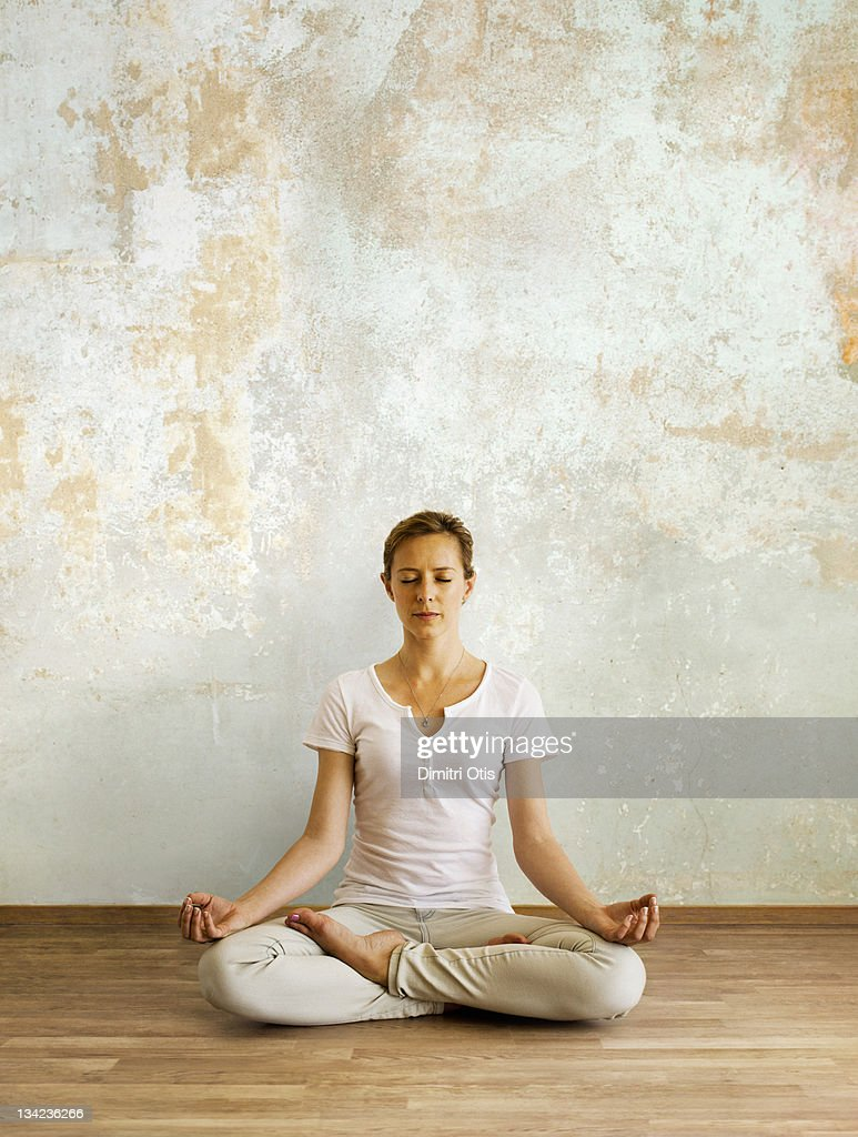 Woman in deep meditation seated in lotus position : Stock Photo