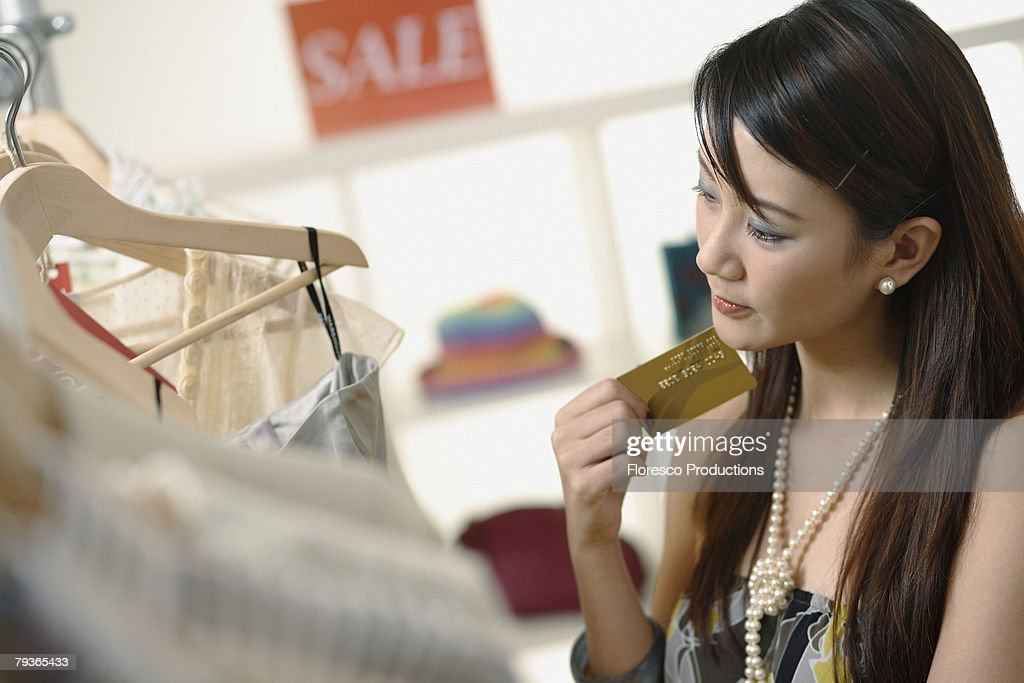 Woman in department store holding credit card : Stock Photo