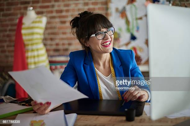 Woman in design studio holding paperwork using computerised sketch pad smiling