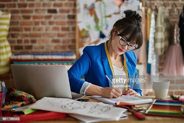 woman in design studio sitting at desk sketching fashion design - デザイナー服 ストックフォトと画像