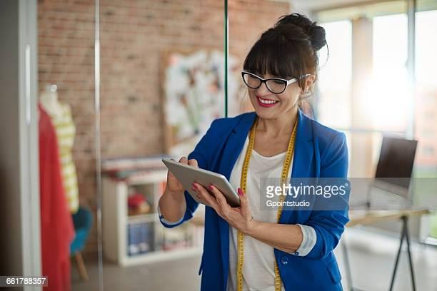 Woman in design studio using digital tablet smiling