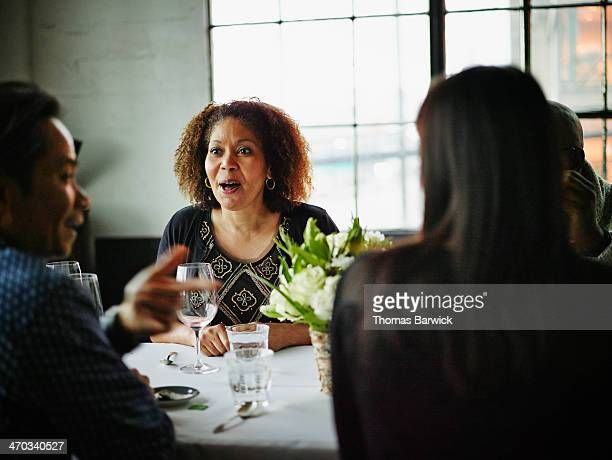 Woman in discussion with friends after dinner