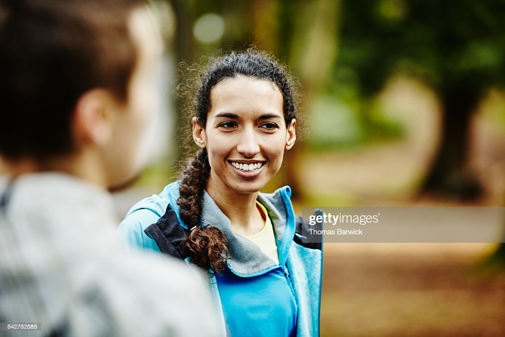 Woman in discussion with friends after trail run : Stock Photo