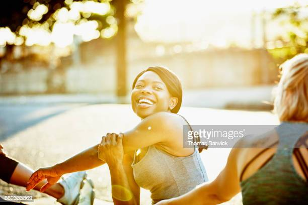 Woman in discussion with friends while stretching