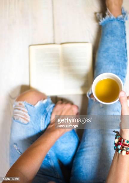 Mujer en Jeans apenado se relaja con libro y té