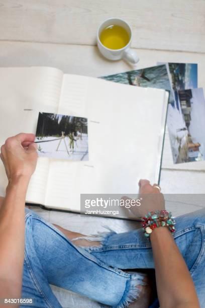 Mujer en Jeans apenado se relaja con té y álbum de fotos