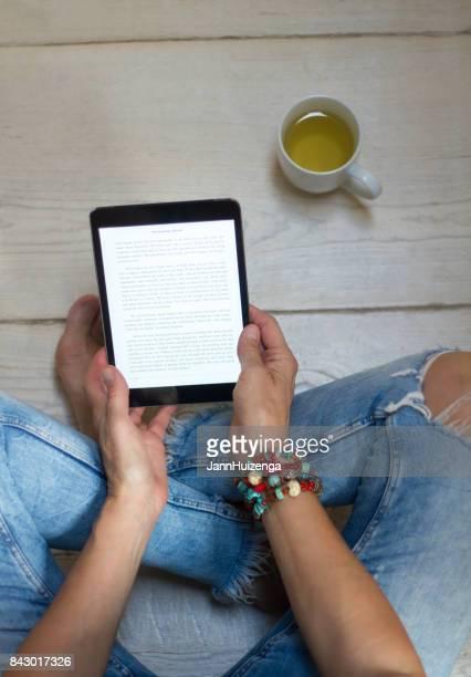 Mujer en Jeans apenado se relaja con tabletas y té