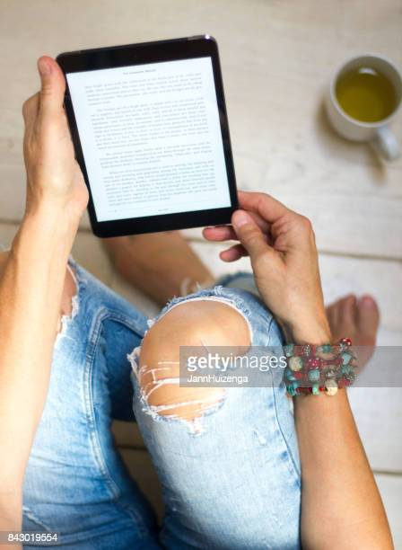 woman in distressed jeans relaxes with tablet and tea - e reader stock pictures, royalty-free photos & images