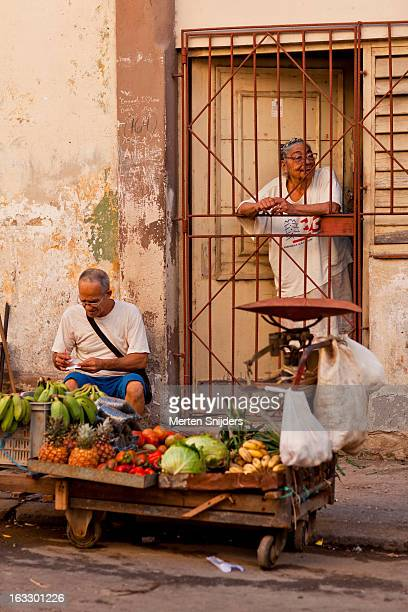 woman in door behind fruit stand - merten snijders stock pictures, royalty-free photos & images