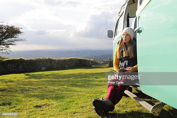 Woman in door of camper on moors reading a book