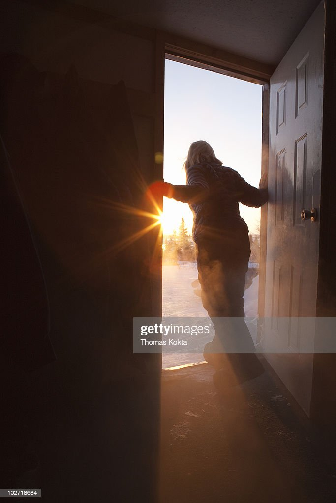 Woman in doorway looking outside : Stock-Foto