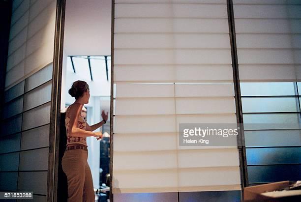 Woman in doorway waving to someone inside