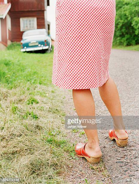A woman in dress and clogs