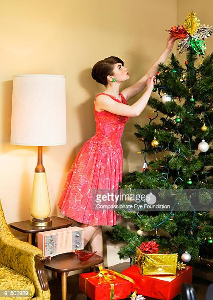 woman in dress decorating a christmas tree