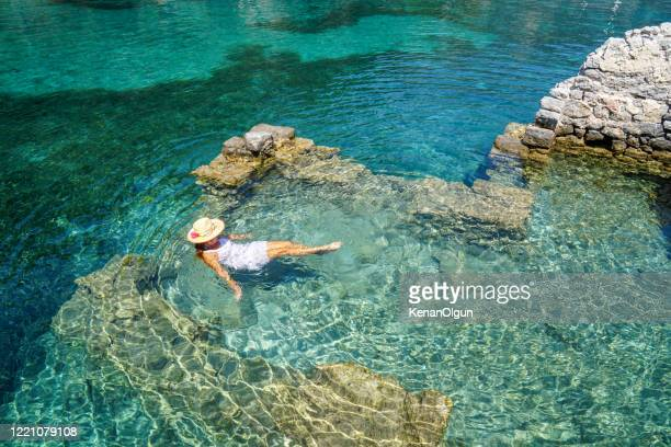 woman in dress floating on the clean sea. - kas stock pictures, royalty-free photos & images