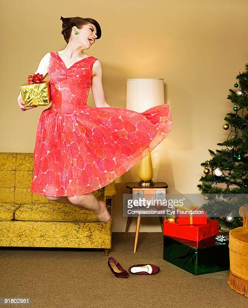 woman in dress jumping while holding a gift
