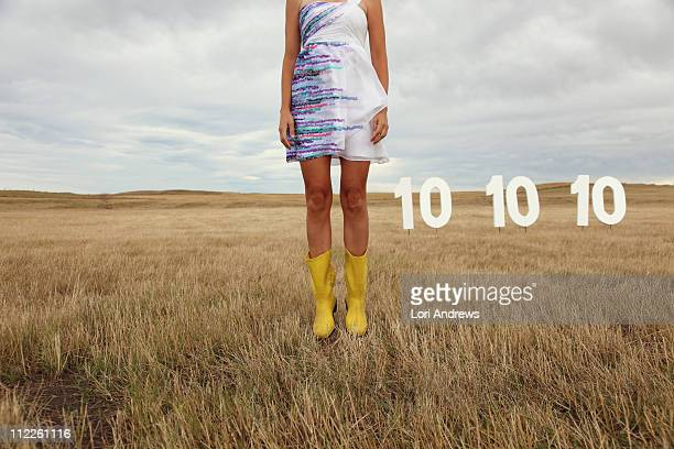 Woman in dress jumps in field