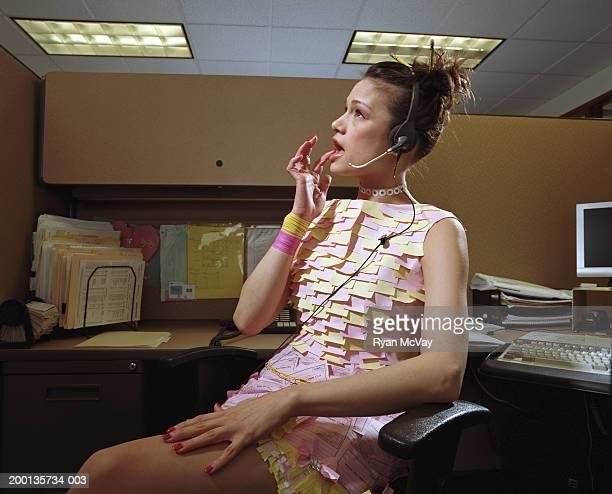Woman in dress made of office supplies, at desk, wearing headset