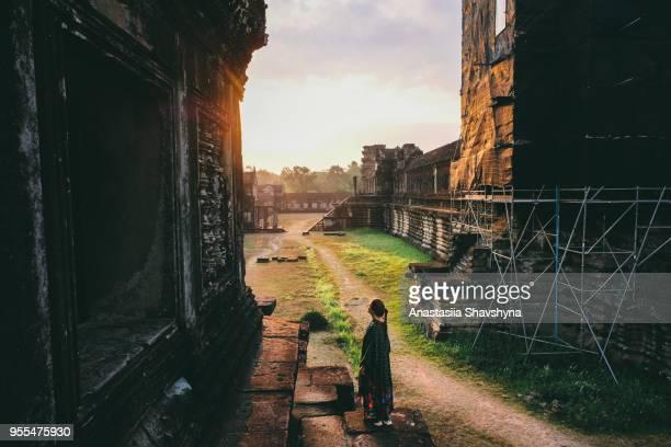 ドレスを着た女性が明るいカンボジアのアンコール ワットの日の出を満たしています。 - 遺跡 ストックフォトと画像