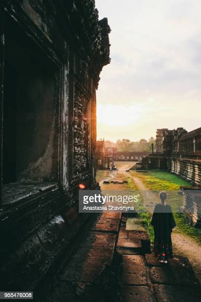 Woman in dress meets bright sunrise at Angkor Wat in Cambodia