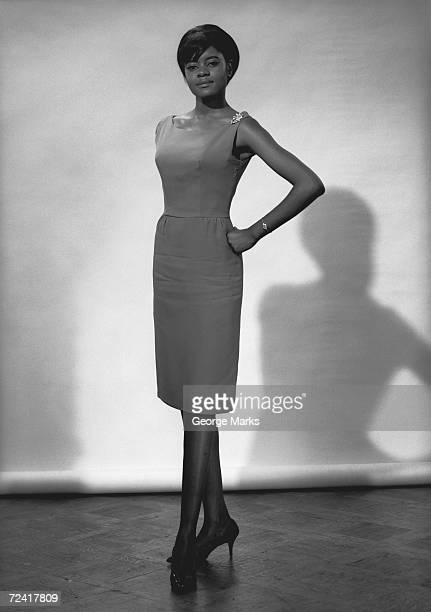 Woman in dress posing in studio, (B&W), portrait