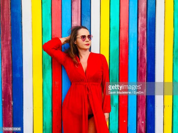 woman in dress standing against multi colored wall - lady madeleine stock-fotos und bilder