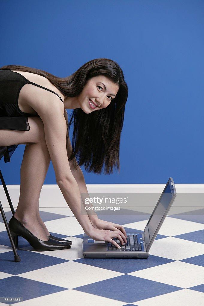Woman in dress using laptop on the floor : Stockfoto