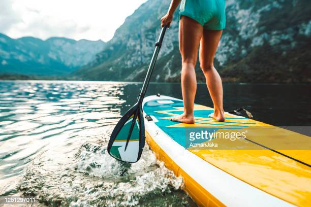 woman in early 30s paddleboarding on lake bohinj in slovenia - paddling stock pictures, royalty-free photos & images
