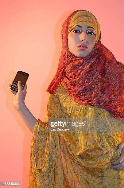woman in ethnic dress showing off her mobile phone - depczyk stock pictures, royalty-free photos & images